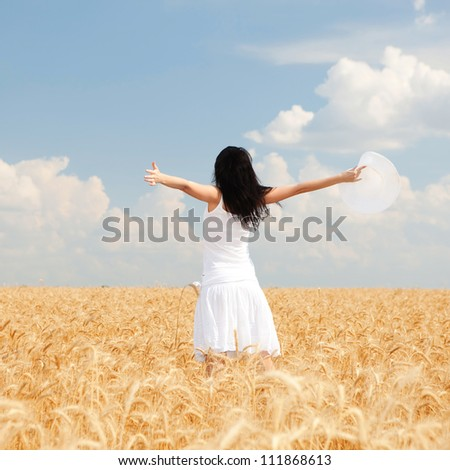 Woman in golden wheat - stock photo
