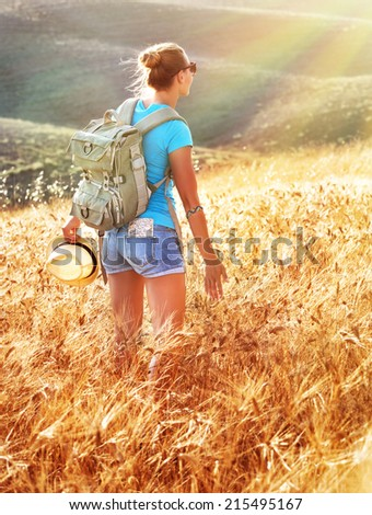 Woman in golden wheat field in sunset, backpack travel to European countryside, active lifestyle, active summer vacation concept, Italy - stock photo