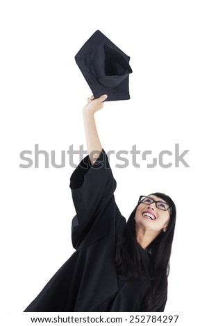 Woman in graduation gown expressing success. isolated on white background - stock photo
