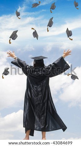woman in graduation gown with her hands in the air - stock photo