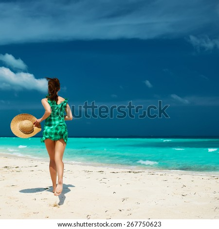 Woman in green dress at tropical beach - stock photo