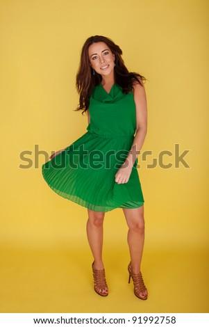 Woman In Green Dress Twirling Her Skirt, full length portrait on yellow studio background - stock photo