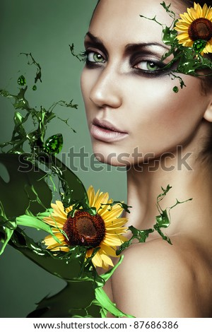 woman in green plant splash with sunflower - stock photo