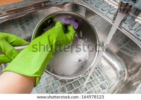 woman in green rubber gloves washing dishes in the sink under water - stock photo