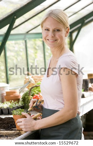 Woman in greenhouse raking soil in pot smiling - stock photo