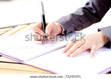 woman in grey write by pen on paper. Businesswoman signs. Isolated on white background - stock photo