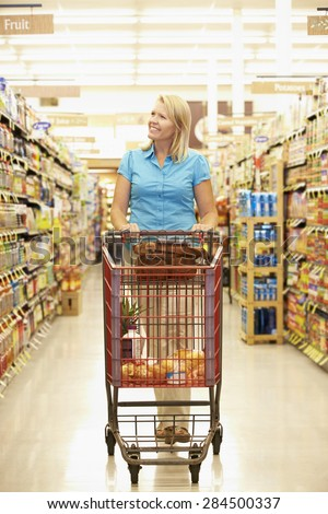 Woman In Grocery Aisle Of Supermarket - stock photo