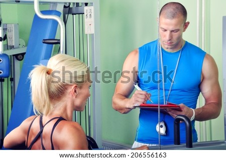 Woman in gym exercising with personal fitness trainer - stock photo