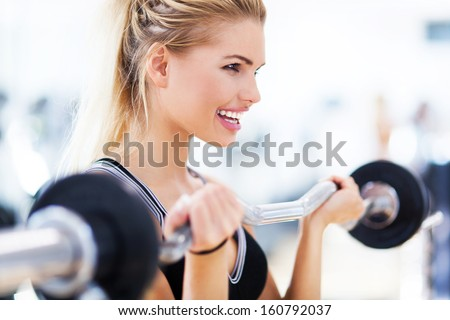 Woman in gym lifting weights - stock photo