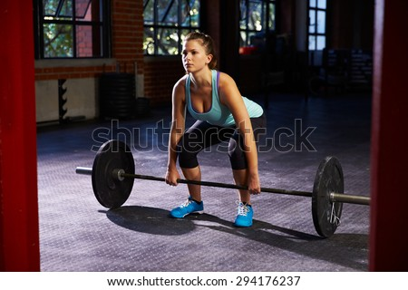 Woman In Gym Preparing To Lift Weights - stock photo