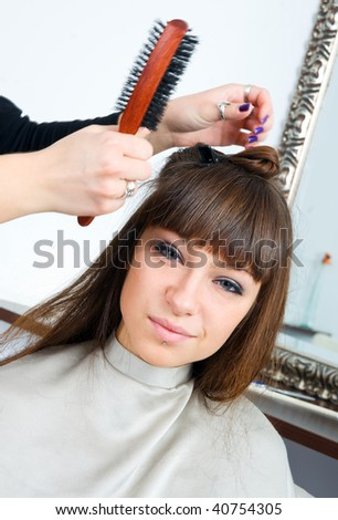 woman in hair salon having treatment with hair brush - stock photo