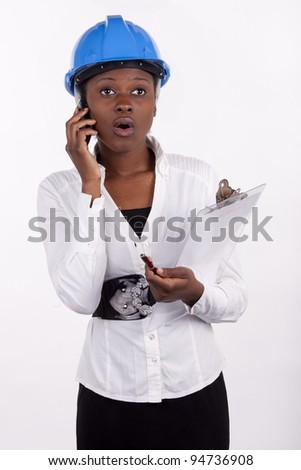 Woman in hard-hat looking shocked by news. - stock photo