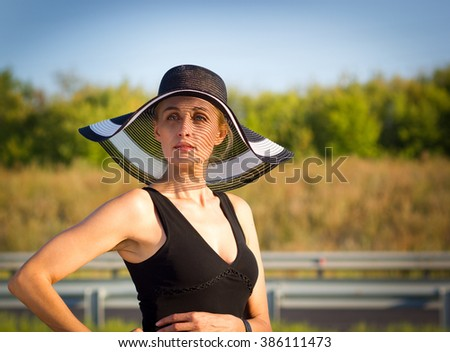 Woman in hat on the road - stock photo
