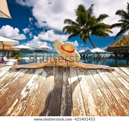 Woman in hat relaxing at the pool - stock photo