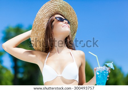 Woman in hat relaxing at the pool with cocktail - stock photo