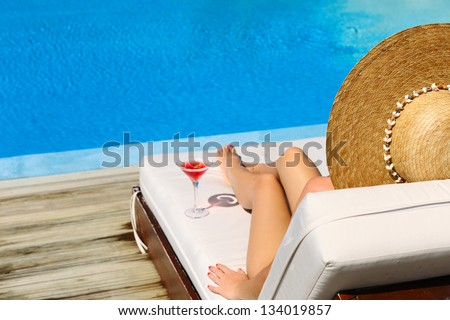 Woman in hat relaxing at the poolside with cosmopolitan cocktail - stock photo
