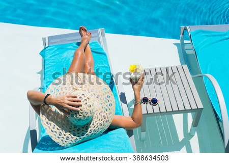 Woman in hat relaxing at the poolside with pina colada cocktail - stock photo