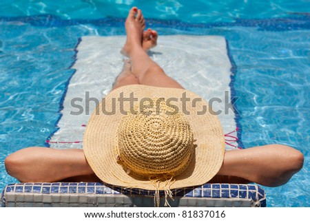 Woman in hat relaxing on holiday on swimming pool bed - stock photo