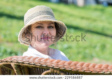 Woman in hat sitting on a wicker bench  - stock photo