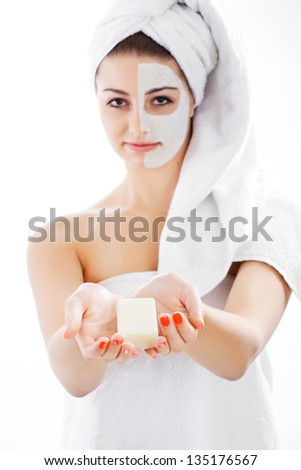 Woman in headband with lifting cream applied on a half of her face take soap, isolated on white - stock photo