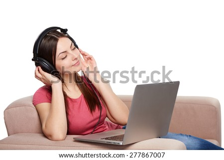 Woman in headphones enjoying music with closed eyes sitting on sofa with laptop, over white background - stock photo