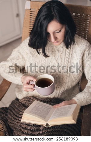 Woman in her living room reading book and drinking tea - stock photo