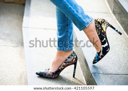 woman in high heel shoes and blue jeans on stairs outdoor shot