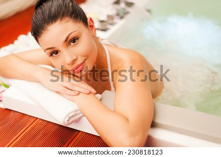 Woman in Jacuzzi. Attractive young woman relaxing in hot tub and looking at camera - stock photo