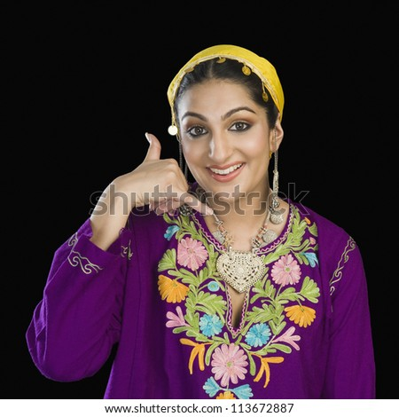 Woman in Kashmiri dress showing call me gesture - stock photo