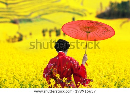 Woman in kimono with red umbrella in her hand walking away, view from back - stock photo