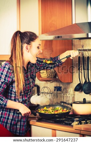 Woman in kitchen cooking stir fry frozen vegetables and tasting. Girl frying making delicious risotto. Dinner food meal. - stock photo