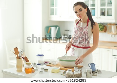 Woman in kitchen during cooking biscuits - stock photo