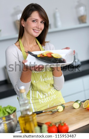 Woman in kitchen holding fish dish - stock photo