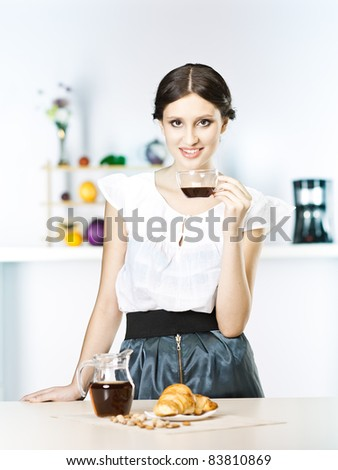 Woman in kitchen with tea in kitchen - stock photo