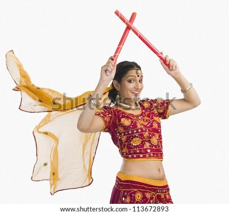 Woman in lehenga choli performing dandiya dance - stock photo