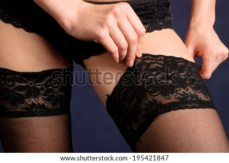 Woman in lingerie wearing black erotic stockings - stock photo