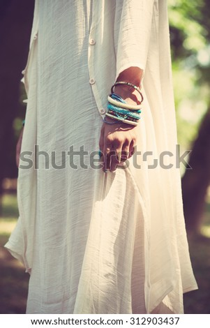 woman in long linen ivory color dress focus on hand with lot of bracelets outdoor shot natural light - stock photo