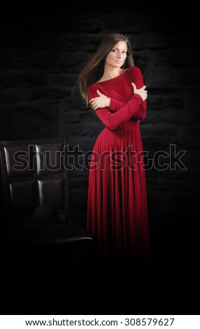 Woman in long red dress, studio portrait, dark background  - stock photo