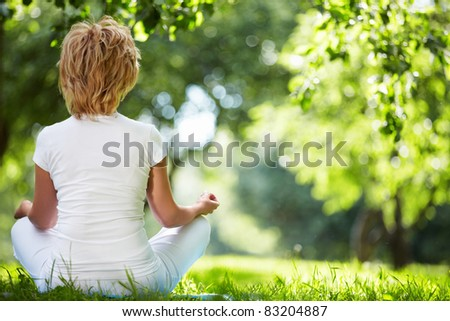 Woman in lotus position outdoors - stock photo