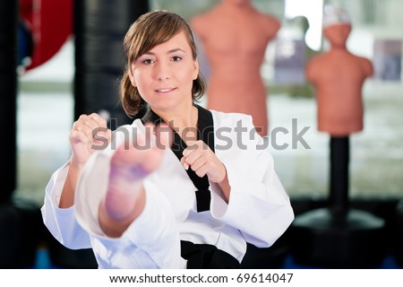 Woman in martial art training in a gym, she is doing a taekwondo front kick - stock photo