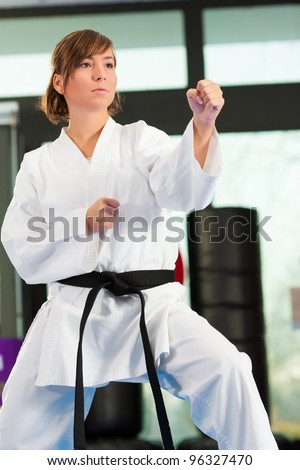 Woman in martial art training in a gym, she is wearing a black belt - stock photo