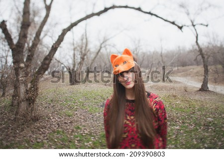 woman in mask of a fox, in the park - stock photo