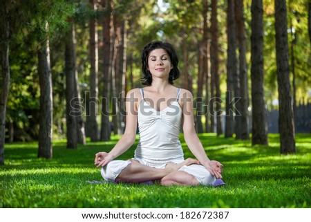 Woman in meditation pose on the green grass in the park around pine trees - stock photo