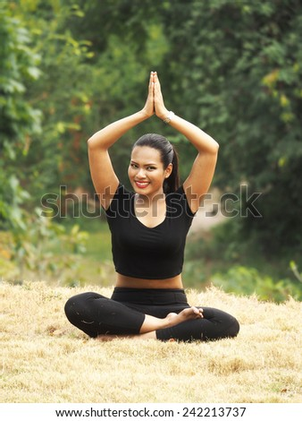 Woman in meditation pose Yoga on the green grass - stock photo