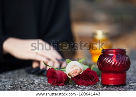 Woman in mourning arranging flowers and candles on the gravestone - stock photo