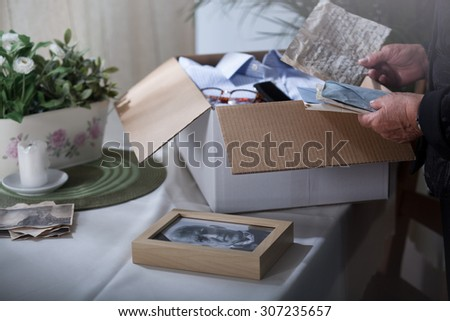 Woman in mourning packing remembrances after dead husband - stock photo
