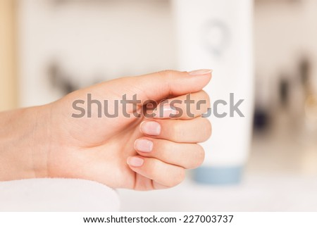 Woman in nail salon receiving manicure. closeup image of female hands and fingers resting on towel - stock photo