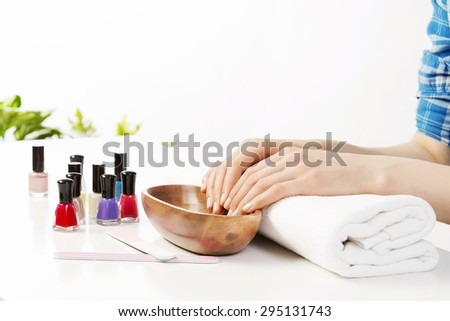 Woman in nail salon with hails in bath - stock photo