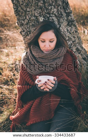 Woman in nature holding cup with tea or coffee - stock photo