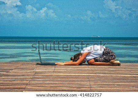 Woman in office suit doing yoga on the wooden floor with laptop. Young Lady has practice on the beach in front of sea view. - stock photo